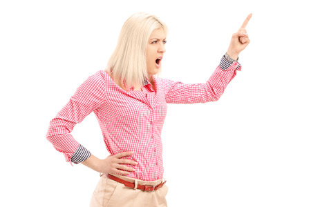 threats: Violent young woman shouting and pointing with finger isolated on white background Stock Photo