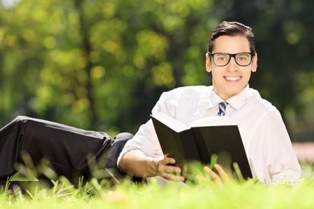 Young male lying on a green grass with book and looking at camera in a park photo