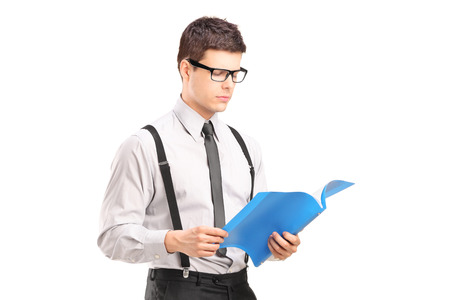 fascicule: Young man reading papers, isolated on white background Stock Photo