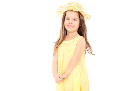 kids dress: Little girl in yellow dress looking at camera isolated on white