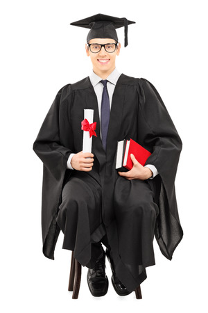 Young male graduate student sitting on chair and holding a diploma isolated on white  photo