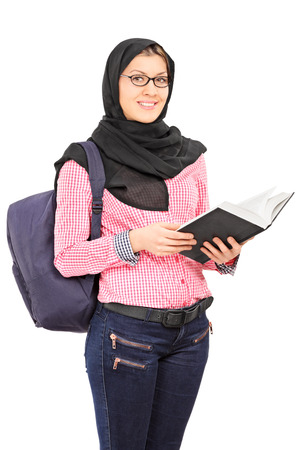 Female Arabic student with backpack holding a book and looking at camera isolated on white background photo