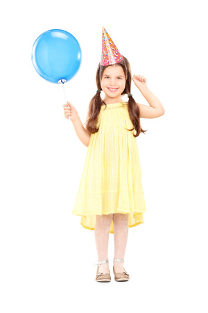 Full length portrait of a cute little girl with party hat holding balloon isolated on white background