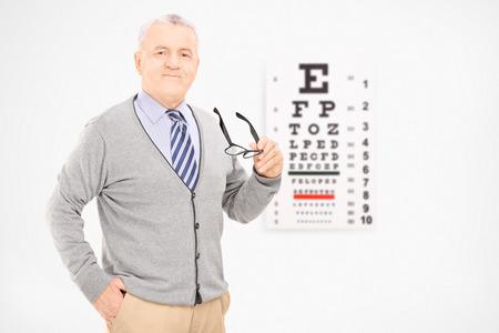 examen de la vista: Hombre maduro que sostiene un par de gafas delante de una prueba de la vista