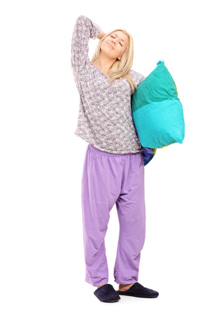 Young woman in pajamas holding a pillow and stretching herself isolated on white background photo