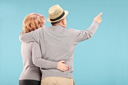 personas abrazadas: Feliz pareja senior mirando algo aislado en el fondo azul, vista trasera