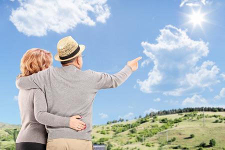 personas abrazadas: Abrazado par mayor que mira hacia el cielo azul, al aire libre