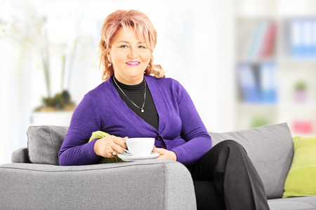Mature lady sitting on a sofa and enjoying a cup of coffee at home photo