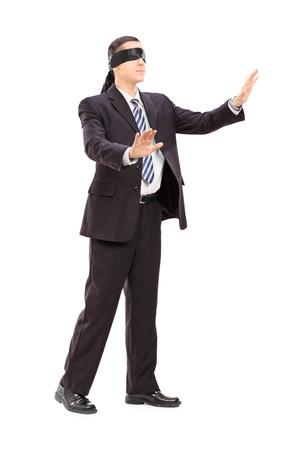 ojos vendados: Retrato de cuerpo entero de un hombre de negocios con los ojos vendados en el juego aislado en el fondo blanco