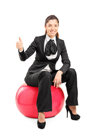 Young businesswoman sitting on pilates ball and giving thumb up isolated on white background photo