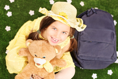 Cute little girl seated on green grass holding a teddy bear with backpack on the ground next to her photo