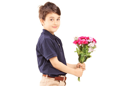 Cute little boy holding bunch of flowers, isolated on white  photo