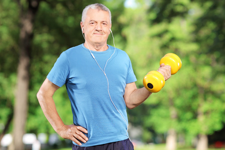 Senior man exercising with weight in a park photo