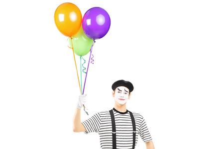 pantomima: Mimo joven que sostiene globos y mirando a la cámara aislada en el fondo blanco