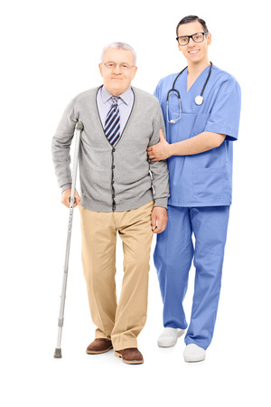 people walking white background: Full length portrait of young doctor helping an elderly gentleman with crutch isolated on white