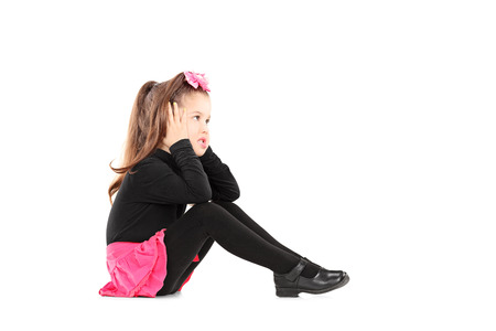 covering: Annoyed little girl covering her ears isolated on white background Stock Photo