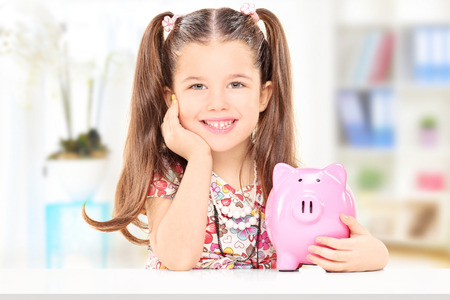 Cute girl sitting at table and holding her savings at home