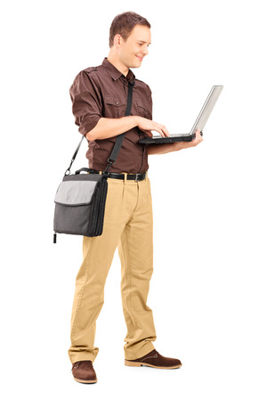 Full length portrait of a young man working on laptop isolated on white background photo