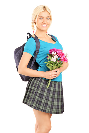 checkered skirt: Young schoolgirl holding bouquet of flowers isolated on white background Stock Photo