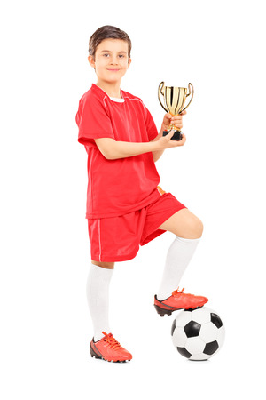 Full length portrait of a junior football player holding a trophy isolated on white background photo