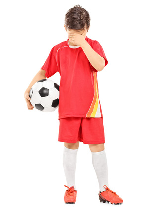 Full length portrait of a sad boy with soccer ball isolated on white background photo