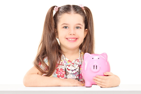 Little girl sitting at table and holding a piggybank isolated on white background Stock Photo