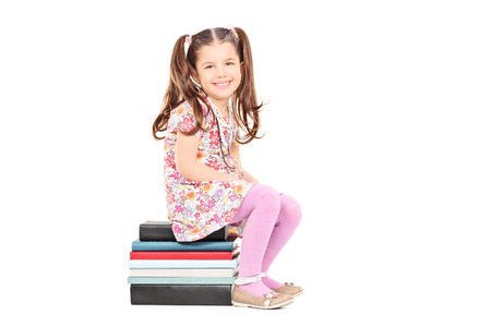 shy girl: Shy girl sitting on a stack of books isolated on white background