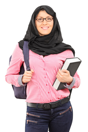 Muslim female student with backpack holding a book isolated on white background photo