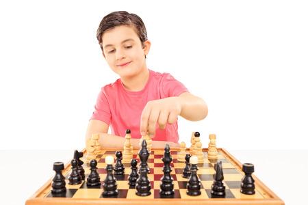 jugando ajedrez: Joven muchacho que juega al ajedrez sentados en una mesa aislada en fondo blanco Foto de archivo