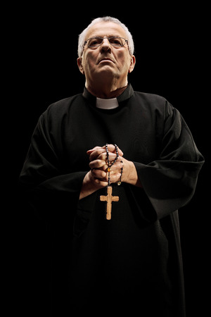 catholic priest: Catholic reverend holding a wooden cross isolated on black  Stock Photo