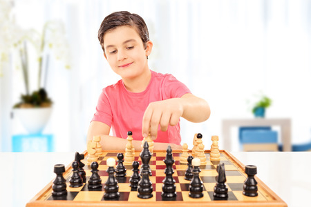 Little boy playing chess seated on a table at home photo