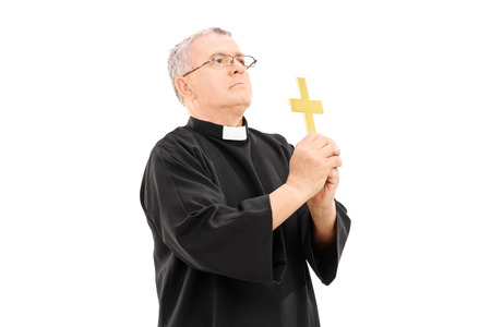 Mature reverend holding a holy cross and praying to god isolated on white  photo
