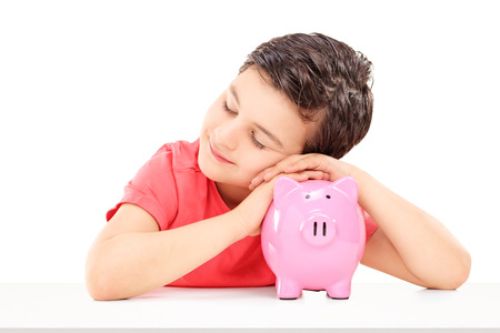 Cute male child sleeping on a piggybank isolated on white  photo