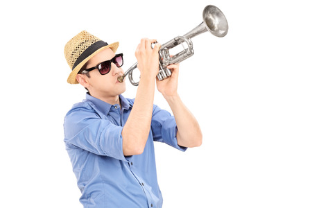 trumpeter: Young male musician blowing into a trumpet isolated on white