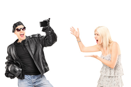 Mad woman yelling at her biker boyfriend isolated on white  photo
