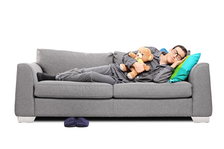 Young man in pajamas sleeping on couch with teddy bear isolated on white
