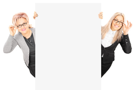Young woman and mature lady with glasses standing behind blank panel isolated on white Stock Photo - 26352732