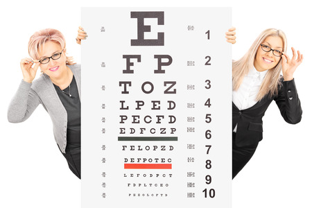 two visions: Young woman and a mature lady with glasses standing behind eyesight test isolated on white