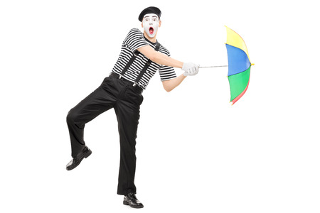 simulating: Full length portrait of a mime artist holding an umbrella simulating being blown by wind isolated on white shot with tilt and shift lens