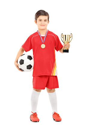 football trophy: Junior football player holding a golden cup isolated on white