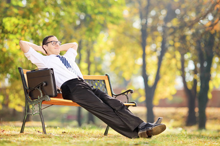 taking a break: Young businessman taking a break after work seated on a bench in park Stock Photo
