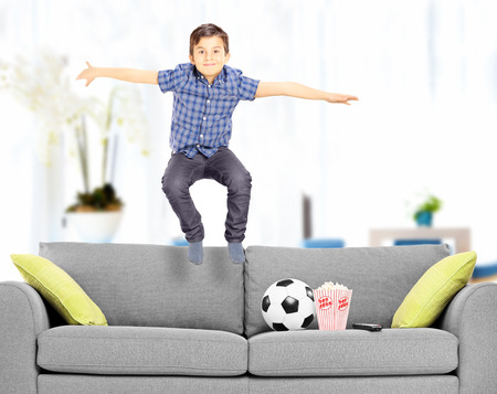 Overjoyed boy jumping on couch at home shot with tilt and shift lens photo