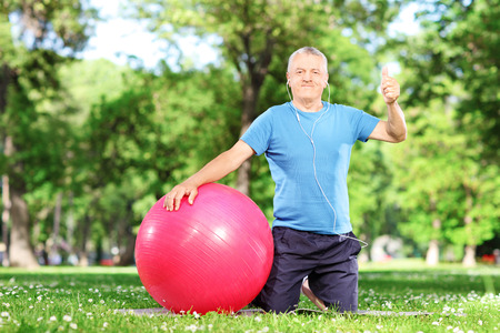 Healthy man giving thumb up seated on an exercise mat in a park photo