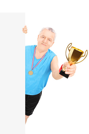 Man in sportswear holding a gold cup behind blank panel isolated on white background photo