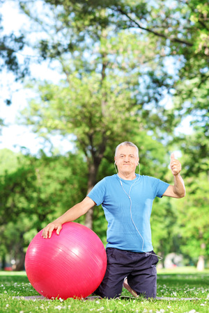 Man sitting in park with pilates ball and listeninig to music
