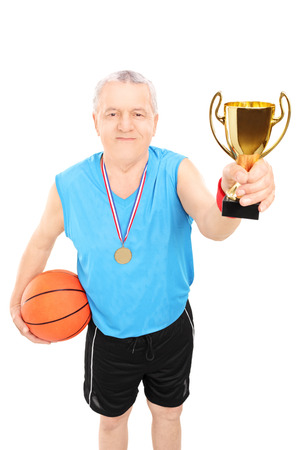 Mature basketball player holding a trophy and wearing gold medal isolated on white background photo