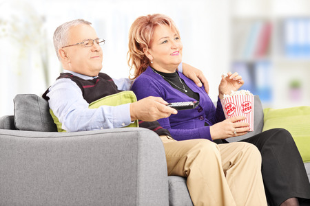 Mature couple eating popcorn and watching tv indoors photo
