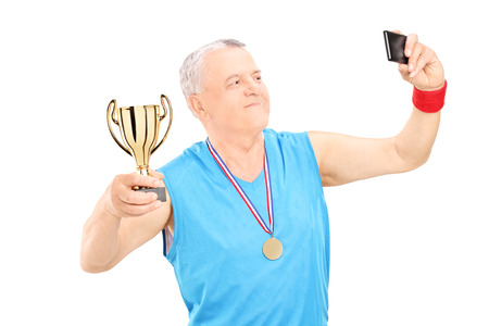 Senior athlete taking selfie with trophy in his hand isolated on white background photo