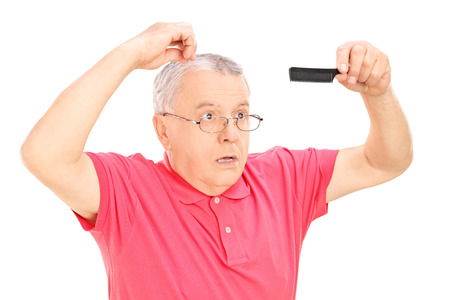 dazzled: Surprised mature man holding a comb isolated on white background
