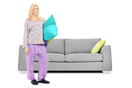 Blond woman in pajamas standing in front of a sofa isolated on white background photo
